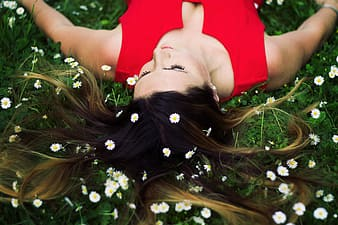 Woman in red sleeveless top lying on green leaf plants