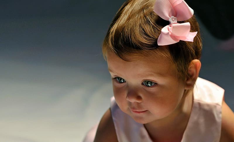 Toddler girl wearing white sleeveless top with pink bow
