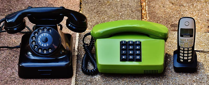Photo of two telephone and cordless phone with dock on surfaec