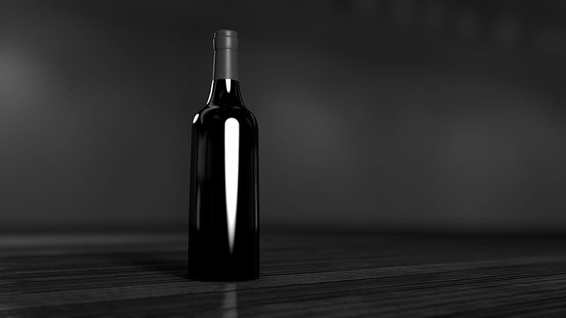 Grayscale photo of bottle on wooden table
