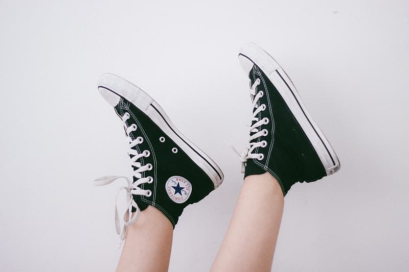 Person wearing black-and-white Converse All-Star high-top sneakers