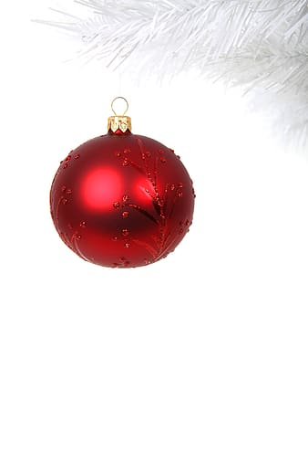 Red bauble hanging on white Christmas tree branch