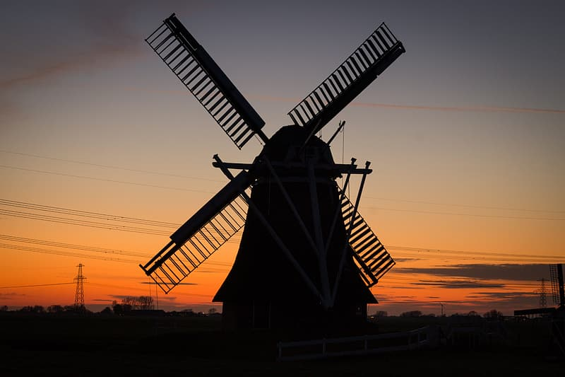 Silhouette of windmill under golden hour