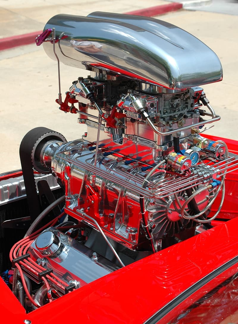 Red and silver engine part on surface