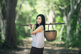 Woman holding stick with basket on her back