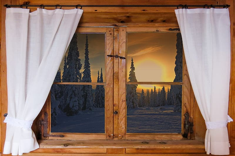 Window with white curtains during golden hour