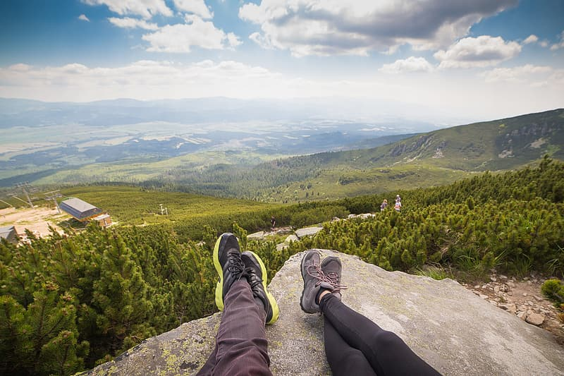 Man and woman on top of hill under white clouds