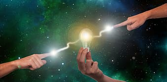 Person holding light bulb with green light