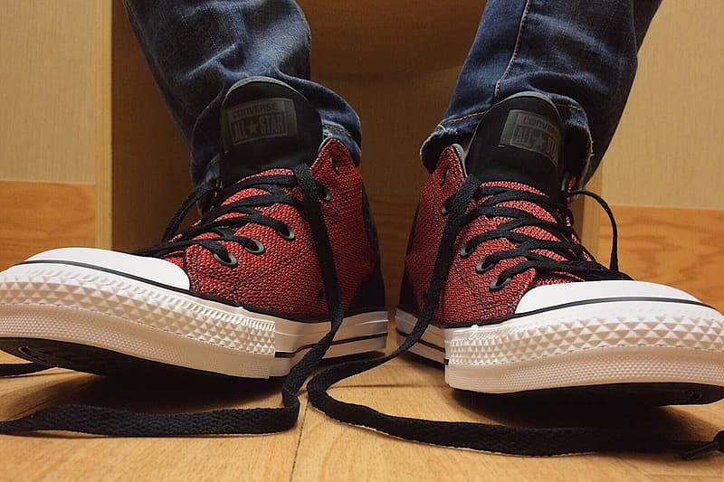 Person wearing untied red-and-black Converse All-Star high-tops