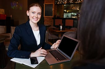 Woman in black blazer sitting at the table with macbook pro