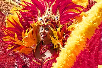 Woman wearing red and yellow costume smiling