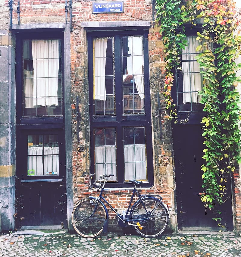 Blue dutch bike on brown concrete brick wall house