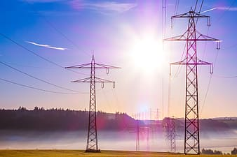 Black electric towers under blue sky during daytime