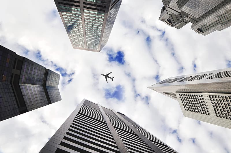 Low angle photography of airplane flying over the high rise buildings during daytime