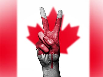 Person's right hand forming peace symbol with Canada flag background