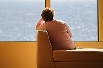 Woman sitting on couch facing window pane with view of body of water