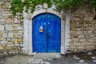 Closed blue wooden French door at daytime
