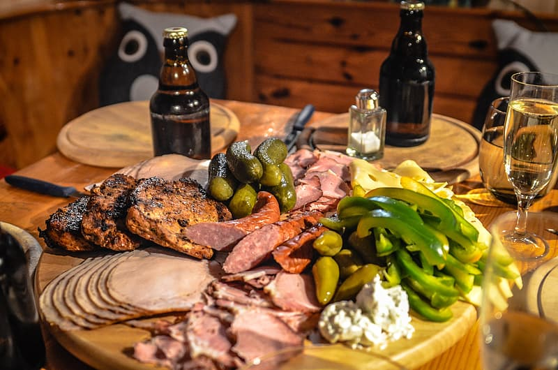 Ham, sausage, green pepper, and grilled pork on round brown wooden chopping board