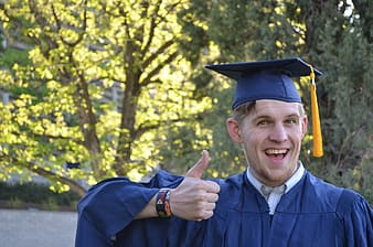 Man in mortarboard and academic dress showing thumbs up sign