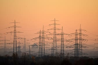 Black electric towers on forest during daytime