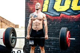 Topless man in black shorts carrying black barbell