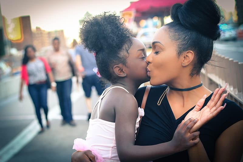 Mother kissing her daughter in cheek while sitting beside the street during daytime