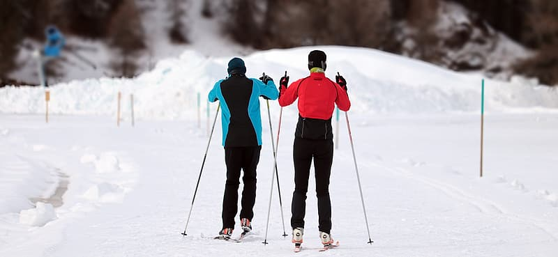 2 person in red jacket and black pants standing on snow covered ground during daytime