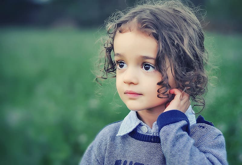 Shallow focus photo of a girl in gray and blue scoop-neck sweater