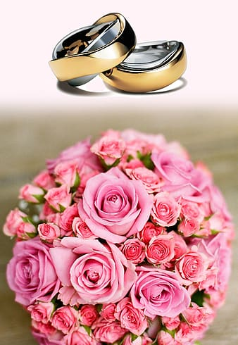 Two gold-colored wedding ring and bouquet of rose
