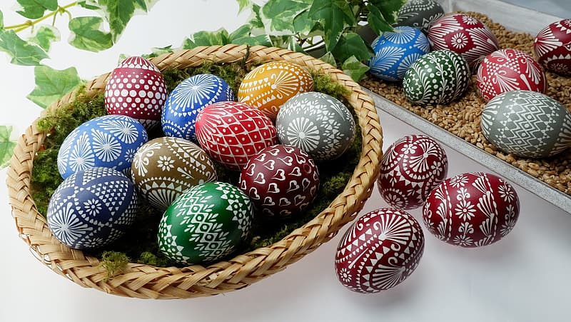 Red blue and white egg on brown woven basket