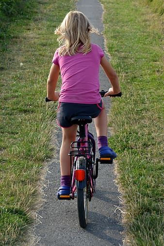 Girl riding bicycle on narrow pathway