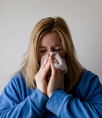 Woman covering her nose with white towel