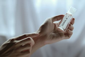 Selective focus photography of person's left hand holding clear essential oil bottle