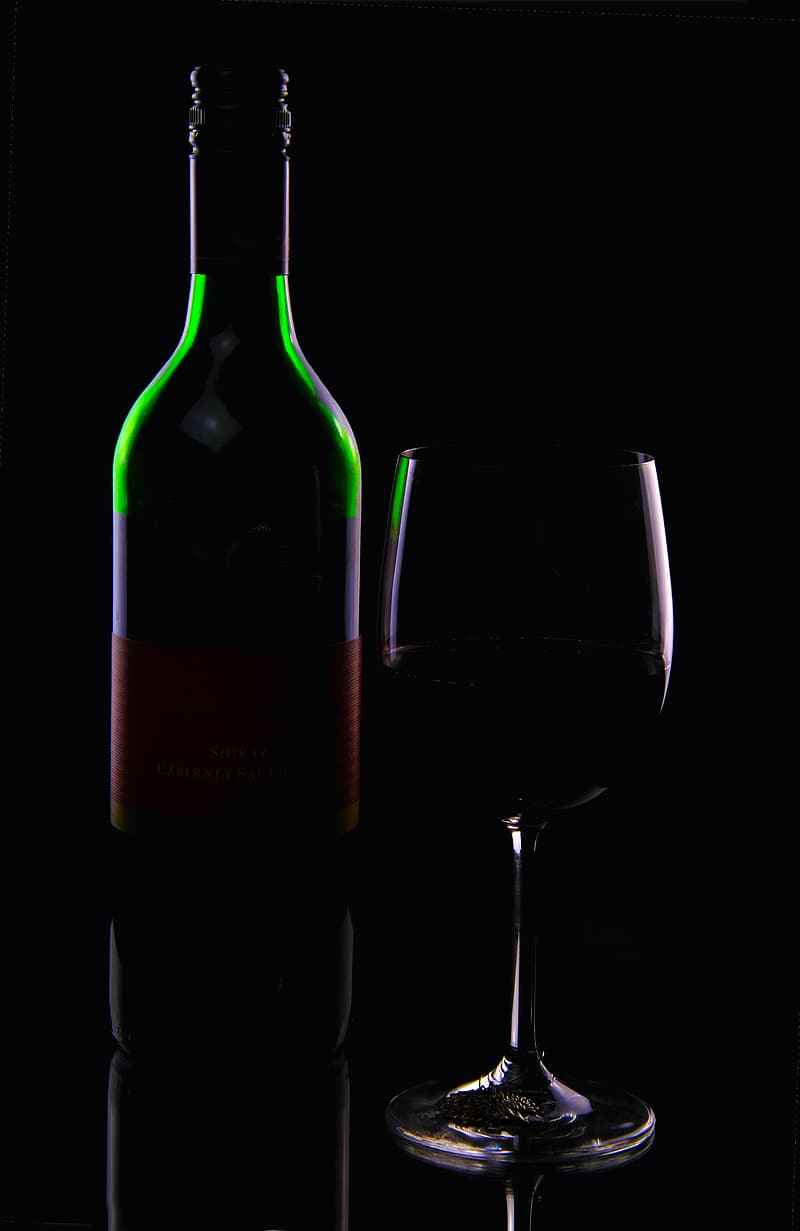 Green purple and red glass bottle beside clear footed glass
