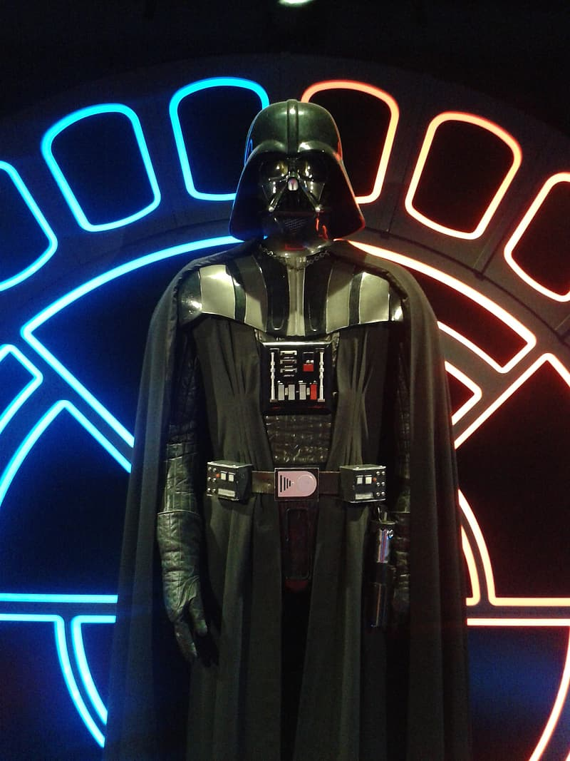 Star Wars Darth Vader standing in front of lighted wall