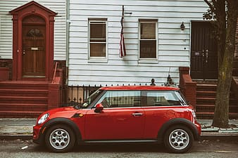 Street shot of a red Mini car sitting on the road in a quiet area of Brooklyn, New York City