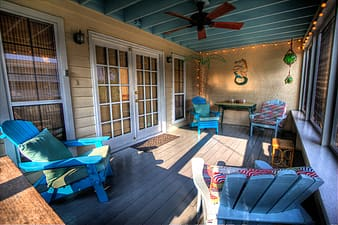 Four blue wooden Adirondack chairs placed near sliding door