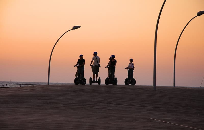 Four person riding personal transporter during golden hour