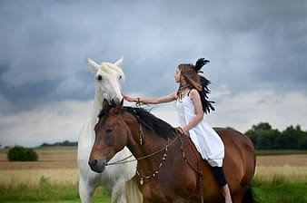 Woman in white tank top riding brown and white horse during daytime
