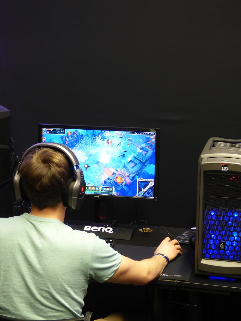 Boy holding computer mouse while playing MMORPG game