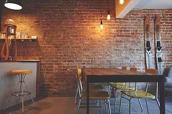 Brown wooden dining table with yellow padded chairs near brick wall \