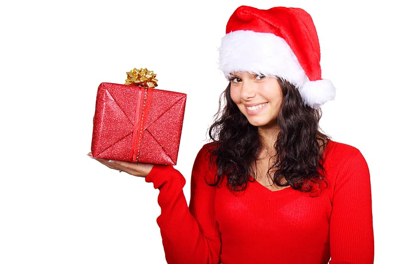 Woman wearing Santa hat while holding red gift