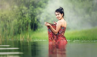 Woman in red and black floral tube dress standing on water during daytime