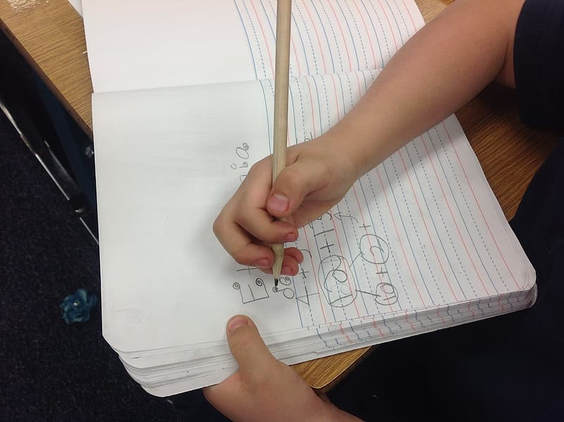 Child holding writing paper and pencil