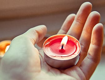 Person holding red tealight candle