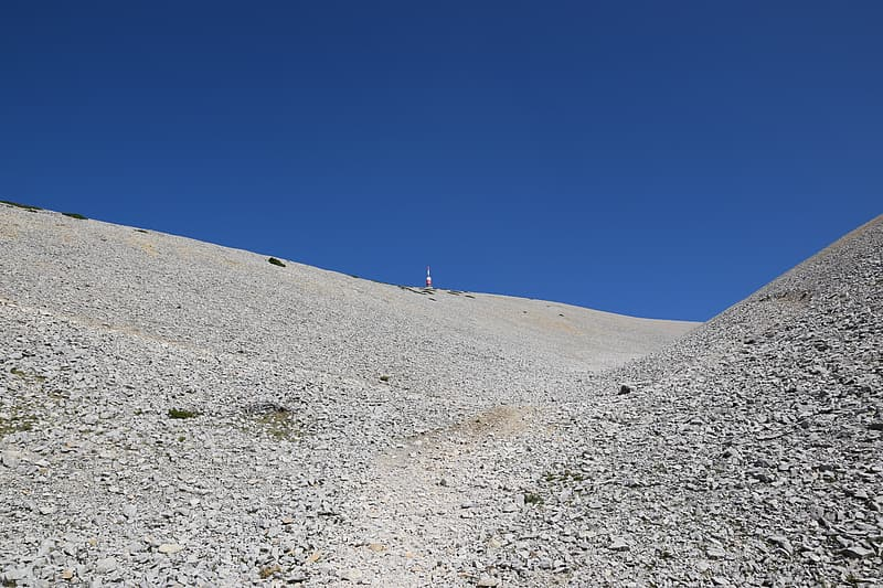 Person in white shirt standing on gray sand under blue sky during daytime