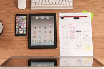 Black iPad beside iPhone on brown wooden table