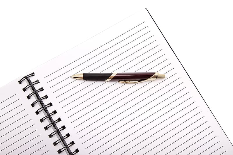 Brown and black click pen on white ruled paper