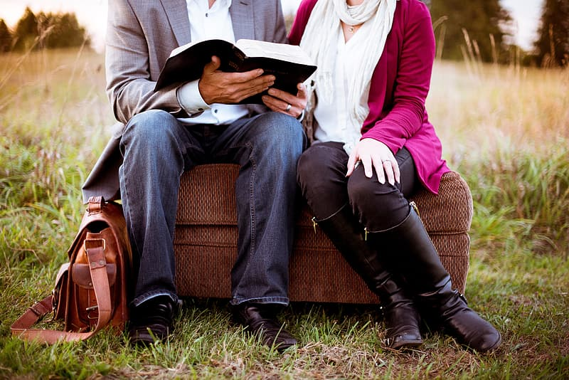 Man and woman sitting on brown wooden bench reading book