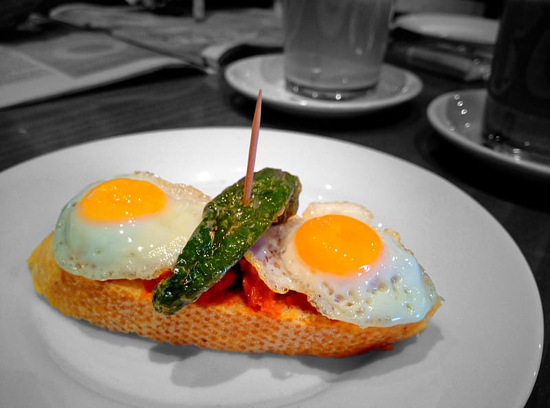 Egg with green leaf on white ceramic plate